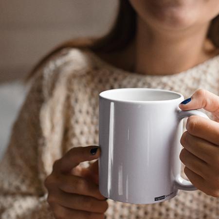 Utilisatrice d'un mug personnalisé à l'image d'une marque